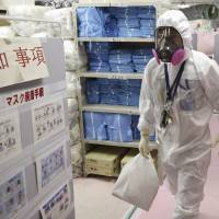 A worker walks through the command center at the Fukushima No. 1 power plant in the town of Okuma in November. | AP