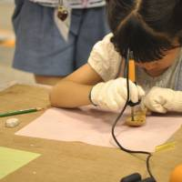 A girl decorates a wooden spoon during a workshop at last year's Yokohama Handmade Marche.