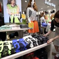 A sales assistant arranges T-shirts at Fast Retailing Co.'s new g.u. store in Tokyo's trendy Shibuya district on June 17. | BLOOMBERG