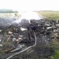 A man works at putting out a fire Thursday at the site of a Malaysia Airlines Boeing 777 plane crash in the settlement of Grabovo in the Donetsk region.   REUTERS