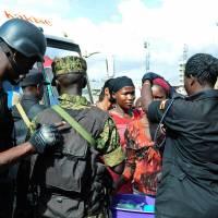 Ugandan soldiers and police perform spot checks on travelers in Kampala on Thursday. | AFP-JIJI