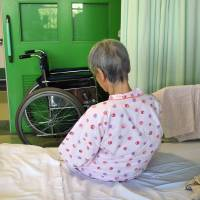 An Alzheimer's patient sits on her bed at a Tokyo hospital in August 2009. | BLOOMBERG