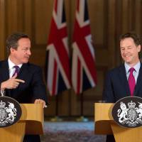 Britain's Deputy Prime Minister Nick Clegg (right) chuckles as Prime Minister David Cameron addresses a joint news conference on emergency surveillance laws at 10 Downing Street in London on Thursday. Britain said it would rush through emergency legislation to force telecommunications companies to retain customer data for a year to protect national security. | REUTERS