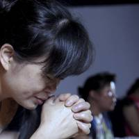 Church members pray in a private room in Jiu'en Tang, a Christian church, in the Shuitou township in Wenzhou in eastern China's Zhejiang province, in the middle of this month. | AP