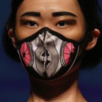 A model wears a Vogmask brand face mask with air filters that provide protection from PM2.5 particles on Tuesday during Hong Kong Fashion Week for Spring/Summer 2015. | REUTERS