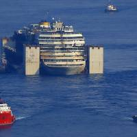 The wreck of the luxury cruise ship Costa Concordia is towed by two tugboats some 45 km off the coast of Viareggio, Italy, on Friday. | AP