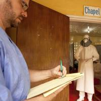 Dr. Kent Brantly (right), of Samaritan's Purse relief organization, is shown in an undated photo wearing protective equipment as he gives orders for medication to Ebola patients, at the ELWA Hospital in Monrovia, Liberia. Brantly, a 33-year-old American doctor, tested positive for Ebola on Saturday. | REUTERS