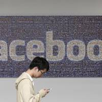 A man walks past a Facebook sign in an office on the Facebook campus in Menlo Park, California, in 2011. British data protection authorities said Wednesday they are investigating revelations that Facebook conducted a psychological experiment to shape the emotions of its users by manipulating the content of their news feeds. | AP