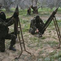 Masked Palestinian militants from Islamic Jihad place homemade rockets before later firing them into Israel on the outskirts of Gaza City, in the Gaza Strip, in December 2008. | AP