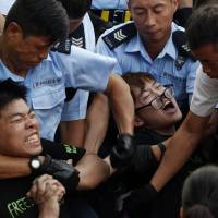 Protesters are taken away by police officers after hundreds of demonstrators staged a peaceful sit-in overnight on a street in Hong Kong's financial district early Wednesday, following a huge rally to show their support for democratic reform. | AP