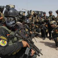 Members of the Iraqi Special Operations Forces prepare for a patrol in the town of Jurf al-Sakhar, south of Baghdad, on June 30. Iraqi troops are battling to dislodge the Islamic State militant group from towns nationwide after its leader declared himself caliph of a new Islamic state in lands seized this month across a swath of Iraq and Syria. | REUTERS