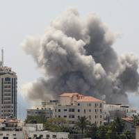 Smoke rises after what witnesses said was an Israeli air strike in Gaza City on Sunday. Hamas militants agreed to a 24-hour humanitarian truce in its conflict in the Gaza Strip, the group's spokesman said, while Israel called off its own 24-hour truce earlier in the day after Hamas fired a volley of rockets into southern and central Israel. | REUTERS
