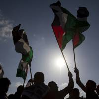 Arab Israeli protesters wave Palestinian flags as they gather to mark the annual Land Day event in the Arab village of Deir Hanna, in northern Israel, in March 2012. | AP