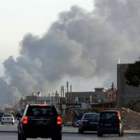 Smoke billows from an area near Tripoli's international airport during fighting between rival factions on Thursday. The United States evacuated its embassy staff under air cover from Libya on Saturday because they faced a 'real risk' from the fierce fighting around the airport, Secretary of State John Kerry said. | AFP-JIJI