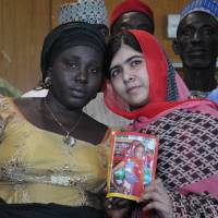 Pakistani activist Malala Yousafzai holds a picture of kidnapped schoolgirl Sarah Samuel with the girl's mother, Rebecca Samuel, during a visit to Abuja on Sunday. | AP