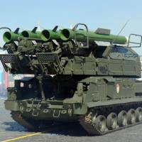 A Russian air defence Buk-2M armored vehicle launcher takes part in a Victory Day parade in Red Square, Moscow, in May 2013. A Russian-made surface-to-air missile has emerged as the most likely cause of the downing of Malaysian Airways Flight MH17 in Ukraine, analysts said on Friday. | AFP