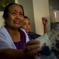 Indonesian Yuriah Tanzil (left), sister of Ninik Yuriani, a passenger aboard Malaysia Airlines Flight MH17, shows a photograph of her sister at the family residence in Jakarta on Friday after the plane crashed in Ukraine, killing all 298 people on board. | AFP