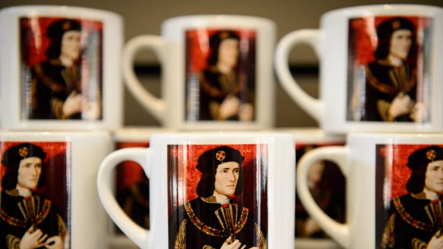 Souvenir coffee mugs showing King Richard III are displayed Thursday at the new visitor center on the site where his remains were discovered in Leicester, central England.