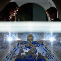 Visitors look a replica skeleton of King Richard III on Thursday displayed at the new visitor center on the site in the city of Leicester where his remains were discovered in 2012. | AFP