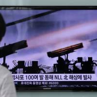 People watch a TV news program reporting on North Korea's artillery shells at Seoul Railway Station in the South Korean capital on Monday. The superimposed letters on the screen read: 'North Korea fired about 100 artillery shells into NLL (Northern Limit Line) North Korea area on East Sea.' | AP