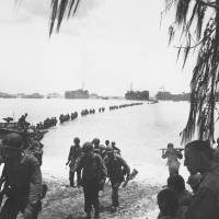 U.S. Army reinforcements disembark from LST's and cross a coral reef toward a beach on Saipan in the Mariana Islands in June 1944. | PVT. EDWARD Laudansky (U.S. Army)/AP