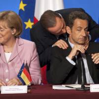 Italian Prime Minister Silvio Berlusconi (rear) talks with French President Nicolas Sarkozy following a summit on the international financial crisis at the Elysee Palace in Paris on Oct. 4, 2008. At left is German Chancellor Angela Merkel. | REUTERS
