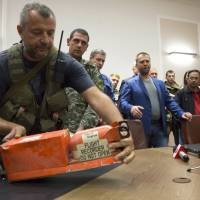 A pro-Russian fighter places a black box from the downed Malaysia Airlines Flight MH17 on a table before handing it over to Malaysian government representatives in the eastern Ukrainian city of Donetsk on Tuesday.   AP