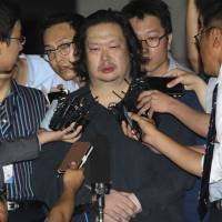 Yoo Dae-kyun (center), the eldest son of the tycoon at the head of the company which operated the sunken passenger and cargo ferry Sewol, is surrounded by reporters after he was taken to Incheon District Prosecutor's Office in Incheon, South Korea, on Friday. South Korean police detained Yoo after two months on the run, and three days after his billionaire father was confirmed dead. | AP