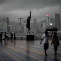 As a thunderstorm caused by Super Typhoon Rammasun dumps heavy rain on Hong Kong on Friday, people walk near the waterfront. Behind, on the other side of the harbor, is Hong Kong Island. | AFP-JIJI