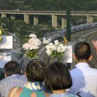 Relatives of victims of the Santiago de Compostela train crash watch a train passing at the site of the accident in Angrois at the same time one year after during a tribute marking the first anniversary Thursday. An eight carriage train was hurtling around a bend at 179 kph (111 mph), more than twice the speed limit, when it derailed on July 24, 2013, killing 79 people and injuring many more. | AFP-JIJI
