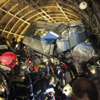 Rescuers work in a tunnel after a train derailed between two subway stations in Moscow on Tuesday. | AP