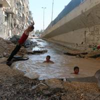 In Syria's Aleppo, children swim in bomb craters