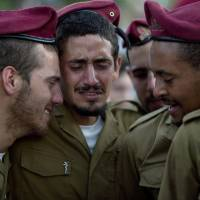 Israeli soldiers from the Paratroopers Brigade mourn over the grave of Sgt. Bnaya Rubel during his funeral at the military cemetery in Holon, Israel, on Sunday. Rubel was killed while fighting Palestinian militants in Gaza on Saturday. | AP
