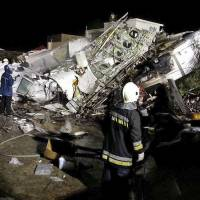 Rescue workers survey the wreckage of TransAsia Airways flight GE222, which crashed while attempting to land in stormy weather on the Taiwanese island of Penghu, late Wednesday night. | AP