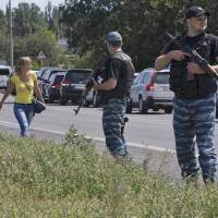 Self-proclamed Donetsk People's Republic policemen guard a convoy of International forensic experts, Dutch and Australian policemen and members of the OSCE mission in Ukraine as it approaches Shakhtarsk, Donetsk region, eastern Ukraine on Monday. | AP