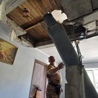 A Ukrainian serviceman inspects an unexploded missile of the type used by pro-Russian militants against Ukrainian forces, in the eastern city of Lysychansk, on Saturday. | AFP-JIJI