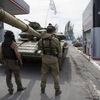Pro-Russian separatist fighters from the 'Donetsk People's Republic' fill their tank with fuel at a gas station in Snizhne, 100 km east of the eastern Ukrainian city of Donetsk, on July 17. | AP