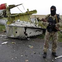 A pro-Russian fighter stands guard at the site of the crashed Malaysia Airlines plane near the eastern Ukrainian village of Grabovo on Friday. | AP