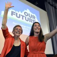 U.S. Democratic Sen. Elizabeth Warren (left) and Kentucky Democratic senatorial candidate Alison Lundergan Grimes wave to supporters at a rally in Louisville, Kentucky, on June 29. | AP