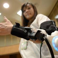 During a news conference in Kawasaki on June 18, an official from the Kawasaki Municipal Government conducts a demonstration using a powered exoskeleton developed by robot-suit venture Cyberdyne. | AFP