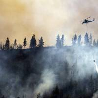 A helicopter drops water on a wildfire Tuesday on a hillside alongside the Entiat River Road, just up canyon from the intersection with Mills Canyon in Entiat, Washington. | AP