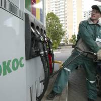 An attendant fills up a car at a Yukos gas station in Moscow on June 18, 2004. The Hague's arbitration court has ruled in favor of a group of shareholders in defunct oil giant Yukos against Russia, awarding compensation of around $50 billion, a source close to the ruling said Tuesday. | REUTERS
