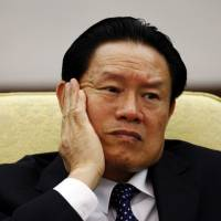 Then China's Public Security Minister Zhou Yongkang reacts as he attends the Hebei delegation discussion sessions at the 17th National Congress of the Communist Party of China at the Great Hall of the People in Beijing on Oct. 16, 2007. | REUTERS