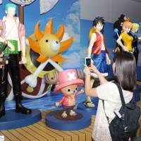 Visitors take pictures of characters from the popular Japanese manga series 'One Piece' at an exhibition at the War Memorial of Korea on Saturday in Seoul. | KYODO