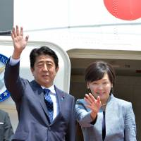 Prime Minister Shinzo Abe and his wife, Akie, wave as they depart for Mexico at Tokyo International Airport at Haneda on July 25. Abe letft for a five-nation tour of Latin America and the Caribbean, including visits to Mexico and Brazil. | AFP-JIJI