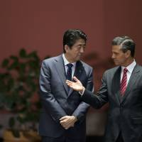 Mexican President Enrique Pena Nieto speaks with Prime Minister Shinzo Abe at the National Palace in Mexico City on Friday. | AP