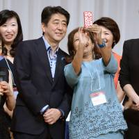 Prime Minister Shinzo Abe poses with participants at the 19th International Conference for Women in Business in Tokyo on Sunday. | KYODO