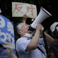 A man shouts slogans through a bullhorn during a protest outside the prime minister's office on Tuesday. | AP