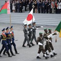 Japanese officers join Belarusian (left) and Beninese soldiers taking part in the annual Bastille Day military parade in Paris on Monday. France issued an unprecedented invitation to all 72 countries involved in World War I to take part in the annual parade. | AFP-JIJI
