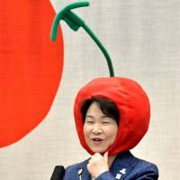 Yamagata Gov. Mieko Yoshimura sports headgear in the shape of a red cherry to promote the local agricultural product while delivering a speech to prefectural officials in the city of Yamagata in April. | KYODO